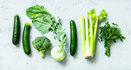 Kitchen - fresh green organic vegetables captured from above (top view, flat lay). Grey stone worktop as background. Healthy diet concept.
