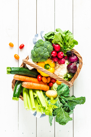 coliflor: Colorful organic spring vegetables in wicker basket - captured from above (top view). White rustic wooden table as background. Layout with free text (copy) space. Fresh harvest from the garden.