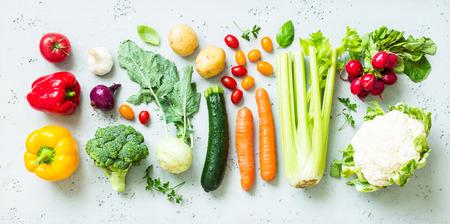Kitchen - fresh colorful organic vegetables captured from above (top view, flat lay). Grey stone worktop as background. Lizenzfreie Bilder