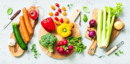 Fresh colorful organic vegetables on wooden chopping (cutting) boards captured from above (top view, flat lay). Grey stone worktop as background. Kitchen - preparing food. Lizenzfreie Bilder