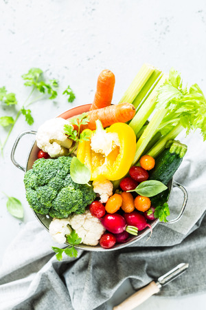 Kitchen - fresh colorful organic vegetables in colander captured from above (top view, flat lay). Grey stone worktop as background. Layout with free text (copy) space.