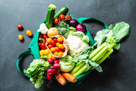 Fresh colorful organic vegetables in green eco shopping bag - captured from above (top view, flat lay). Black chalkboard (blackboard) as background. Lizenzfreie Bilder
