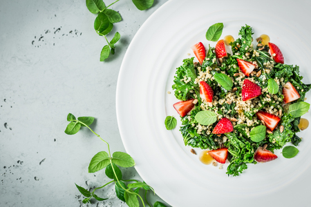 Fresh vegetarian salad with kale, strawberries, quinoa and mint leaves. White plate from above (top view, flat lay). Grey stone background. Layout with free text space. Lizenzfreie Bilder