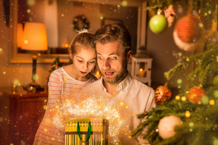 Christmas, family time - caucasian father and daughter looking into a gift (present) bag. Moody warm (gold) light, magical sparkles, cozy atmosphere, by night. Decorated tree and room as background. Stock Photo