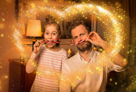 Christmas happy family time - carefree caucasian father and daughter playing (clowning) around while holding candy canes. Moody warm (gold) light, magical sparkles, cozy atmosphere at home.
