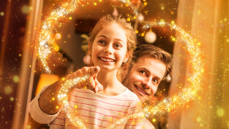 Christmas - smiling father and daughter looking out the window. Waiting for Santa Claus concept. Moody warm (gold) light, magical sparkles, cozy atmosphere, by night. Decorated room as background.