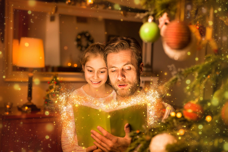 Christmas eve, happy family time - caucasian father reading book for his daughter. Moody warm (gold) light, magical sparkles, cozy atmosphere, by night. Decorated tree and room as background.