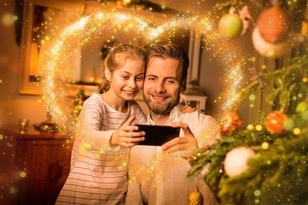 Christmas - happy caucasian father and daughter taking photo of themselves (selfie) on mobile phone (smartphone). Moody warm (gold) light, magical sparkles, cozy atmosphere in decorated room.