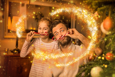 Christmas happy family time - carefree caucasian father and daughter playing (clowning) around while holding candy canes. Moody warm (gold) light, magical sparkles, cozy atmosphere in decorated room. Stock Photo