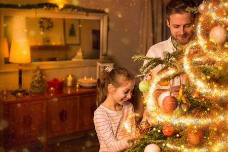 Happy smiling caucasian father and daughter decorate christmas tree at home. Moody warm (gold) light, magical sparkles, cozy atmosphere, by night. Room interior as background.