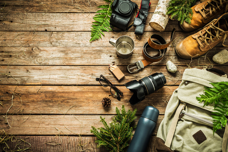 Camping or adventure trip scenery concept. Backpack, boots, belt,   camera on wooden background captured from above (flat lay). Layout with free text (copy) space. Elements of nature around.