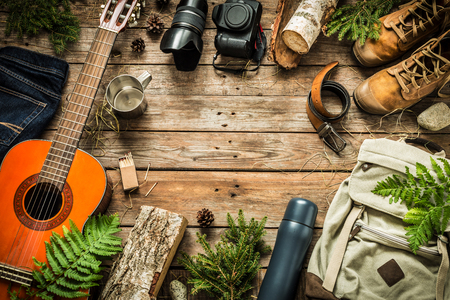 Camping or adventure trip scenery concept. Backpack, guitar, boots, belt,    camera on wooden background captured from above (flat lay). Layout with free text (copy) space. Stock Photo