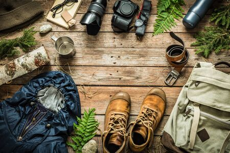 Camping or adventure trip scenery concept. Backpack, jacket, boots, belt,   camera on wooden background captured from above (flat lay). Layout with free text (copy) space.