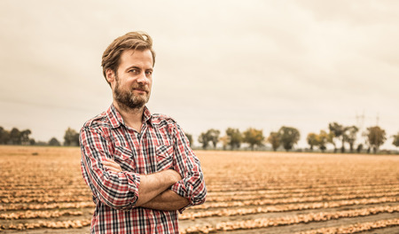 Forty years old caucasian farmer in plaid shirt standing proud in front of onion field. Agriculture - country outdoor scenery (landscape).