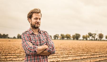 Czterdzieści lat kaukaski rolnik w koszuli w kratę stoi dumny przed pola cebuli. Rolnictwo - krajowa sceneria zewnętrzna (krajobraz).