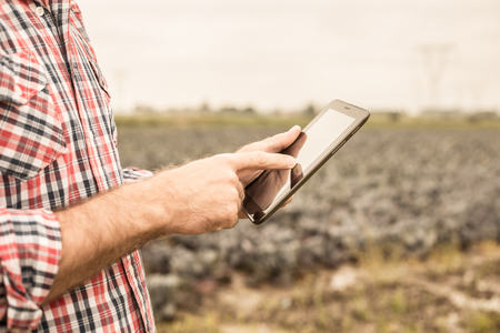 Tablet in farmers hands in front of cabbage field. Modern technology in agriculture - concept. Country outdoor scenery.