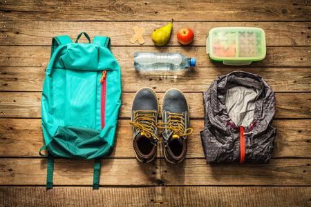 Reizen - inpakken (voorbereiden) voor avontuurlijke schoolreisje-concept. Rugzak, laarzen, jasje, lunchdoos, water en vruchten op houten die achtergrond hierboven wordt gevangen van (leg).
