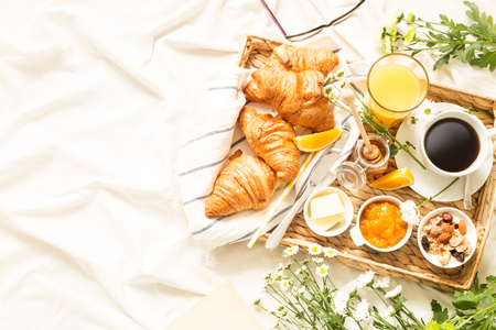 Continental breakfast on white bed sheets. Coffee, orange juice, croissants, jam, honey and flowers on wicker tray from above (top view, flat lay). Background layout with free text (copy) space. Фото со стока