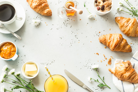 Continental breakfast captured from above (top view, flat lay). Coffee, orange juice, croissants, jam, honey and flowers. Grey stone worktop as background. Layout with free text (copy) space.