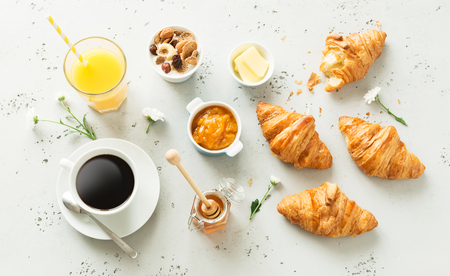 Continental breakfast ingredients captured from above (top view, flat lay). Coffee, orange juice, croissants, jam, honey and flowers. Grey stone worktop as background.