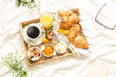 Continentaal ontbijt op witte lakens. Koffie, jus d'orange, croissants, jam, honing en bloemen op rieten dienblad. Het romantische die landschap van de plattelandsochtend van hierboven wordt gevangen (de hoogste vlakke mening, legt).