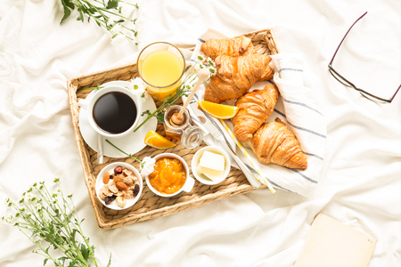 Continental breakfast on white bed sheets. Coffee, orange juice, croissants, jam, honey and flowers on wicker tray. Romantic countryside morning scenery captured from above (top view, flat lay).