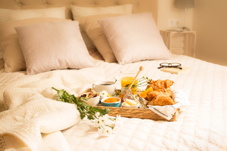 Continental breakfast on bed in elegant bedroom interior. Coffee, orange juice, croissants and flowers on wicker tray. Romantic countryside morning scenery.