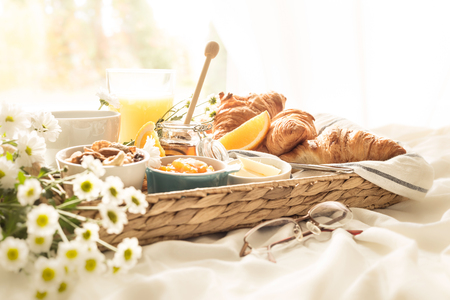 Continental breakfast on white bed sheets. Coffee, orange juice, croissants, jam, honey and flowers on wicker tray. Romantic countryside morning scenery, window as background.