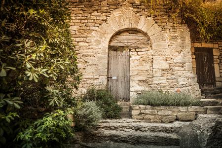 神秘的な庭隅の風景でアーチ (ゲート) と歴史的な石造りの壁します。アーキテクチャの詳細と庭いじりをする - 南ヨーロッパ (フランス)。
