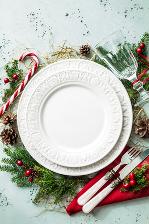 Elegant christmas table setting design captured from above (top view, flat lay). Empty white plate, glass, cutlery, candy cane and decorations. Background layout with free text (copy) space. Stockfoto