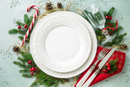Elegant christmas table setting design captured from above (top view, flat lay). Empty white plate, glass, cutlery, candy cane and decorations. Background layout with free text (copy) space. Stock Photo