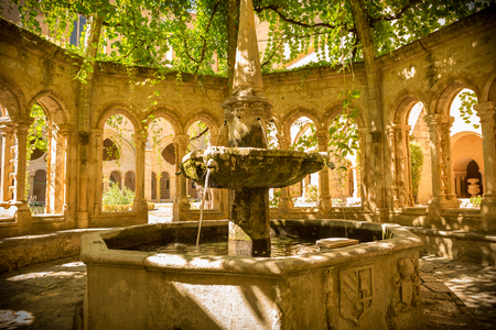 Fountain in Valmagne Abbey arbor, South France. Historic sacral architecture, cistercian order.