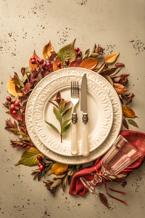 Autumn (fall) or thanksgiving table setting design captured from above (top view, flat lay). White plate, glass, cutlery and decorations (colorful leaves). Dark moody background with free text space.