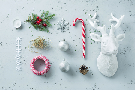 Christmas decorations on grey stone background - winter mood board. Candy cane, pine branch, xmas balls, deer decor and hay. Layout  captured from above (top view, flat lay).
