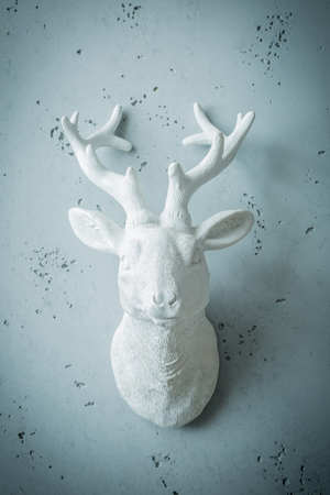 White deer head with antlers - decor or sculpture. Interior decoration on grey wall. Background layout with free text (copy) space.