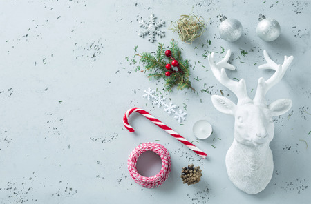 Christmas decorations on grey stone background - mood board. Candy cane, pine branch, xmas balls, deer decor and hay.  Background layout with free text (copy) space - from above (top view, flat lay).