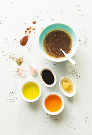 Kochen - dunkelbraune Salatsauce und Rezepturzutaten (Balsamico-Essig, Honig, Olivenöl, Senf, Knoblauch, Salz). Layout von oben aufgenommen (Draufsicht, flach liegend). Grauer Steinhintergrund.