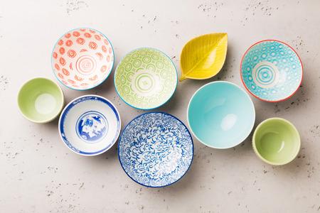 Sammlung leere bunte (Pastell) dekorative keramische Schüsseln auf grauem Steinhintergrund. Layout von oben aufgenommen (Draufsicht, flach liegend).
