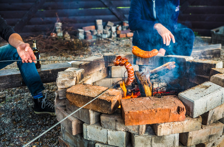 Campfire (bonfire or fire pit) - people roasting sausages. Preparing outdoor meal among friends - picnic.