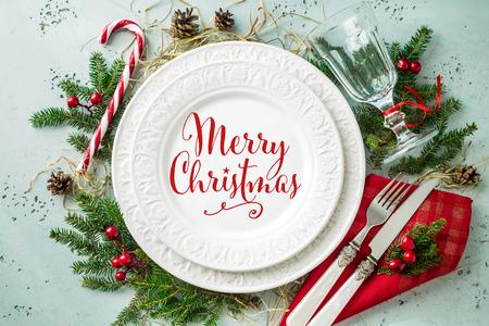 上から撮影したエレガントなクリスマステーブル設定デザイン(上見、フラットレイ)。赤い「メリークリスマス」の看板、ガラス、カトラリー、キャンディ杖と装飾が施された白いプレート。 写真素材 - 90390694