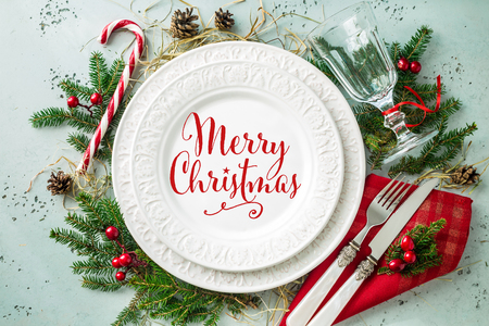 Elegant christmas table setting design captured from above (top view, flat lay). White plate with red 'Merry Christmas' sign, glass, cutlery, candy cane and decorations. Archivio Fotografico