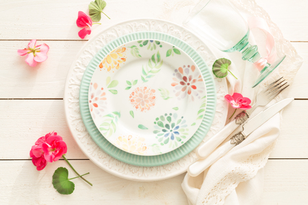Easter, spring or summer table setting design captured from above (top view, flat lay). Ornamental plates, glass, cutlery and flowers. White wooden background. Outdoor garden party or picnic concept. Stock Photo
