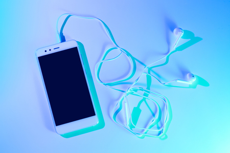 Mobile phone (smartphone) and earphones. Colorful (multicolor tonal transitions) background. Archivio Fotografico