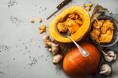 Kitchen - preparing pumpkin (squash) for cooking. Moody rustic still life captured from above (top view, flat lay). Grey stone background with free text (copy) space.