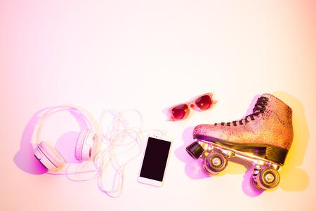 Retro- rosa glittery Rollschuhe, Handy (Smartphone), Kopfhörer und Sonnenbrille nahmen von oben gefangen (Draufsicht, flache Lage). Spaß, Erholung und aktiver Lebensstil - Hintergrund (freier Textraum). Standard-Bild - 92850833