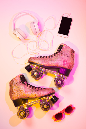 Retro pink glittery roller skates, mobile phone (smartphone), headphones and sunglasses captured from above (top view, flat lay). Fun, recreation and active life style poster concept - summer vibes.