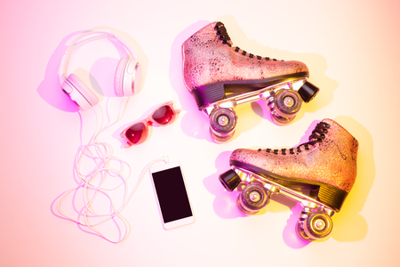 Retro pink glittery roller skates, mobile phone (smartphone), headphones and sunglasses captured from above (top view, flat lay). Fun, recreation and active lifestyle poster concept - summer vibes. Stock Photo