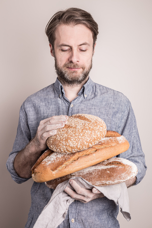 Baker man holding pile of rustic crusty loaves of bread. Small business and slow food concept. Stock Photo