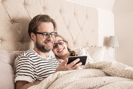 Smiling caucasian father and daughter in pyjamas having fun while using mobile phone (smartphone) in a bed. Morning in a bedroom - happy family time. Imagens
