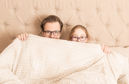 Happy caucasian father and daughter wearing glasses hiding under a duvet in a bed. Morning in a bedroom - happy family time.